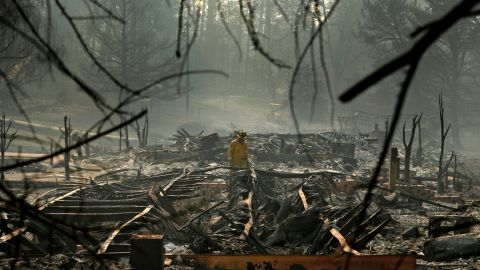 A firefighter searches for human remains on Friday, November 16, in a Paradise trailer park destroyed in the Camp Fire.