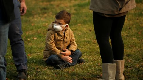A child wears a mask to protect them from smoke as they watch the motorcade of U.S. President Donald Trump pass by on its way to the operations center near Paradise in Chico, California, U.S., November 17, 2018. REUTERS/ Leah Millis