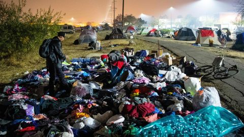 TOPSHOT - Evacuees sift through a pile of clothing at an evacuee encampment in a Walmart parking lot in Chico, California on November 17, 2018. - More than 1,000 people remain listed as missing in the worst-ever wildfire to hit the US state. (Photo by Josh Edelson / AFP)        (Photo credit should read JOSH EDELSON/AFP/Getty Images)