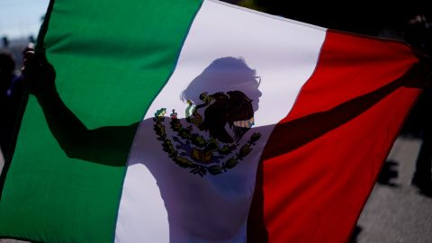 """A demonstrator holds a Mexican flag outside a migrant shelter to protest the presence of thousands of Central American migrants in Tijuana, Mexico, Sunday, Nov. 18, 2018. Protesters accused the migrants of being messy, ungrateful and a danger to Tijuana; complained about how the caravan forced its way into Mexico, calling it an """"invasion,"""" and voiced worries that their taxes might be spent to care for the group as they wait possibly months to apply for U.S. asylum."""