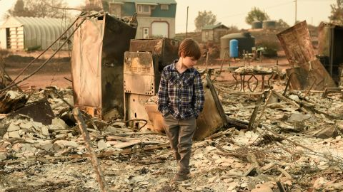 Jacob Saylors, 11, walks through the burned remains of his home in Paradise, California, on Sunday, November 18. His family lost a home in the same spot to a fire 10 years earlier.