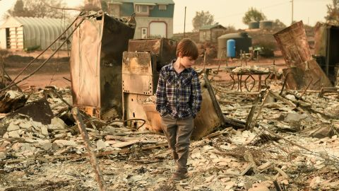 TOPSHOT - Jacob Saylors, 11, walks through the burned remains of his home in Paradise, California on November 18, 2018. - The family lost a home in the same spot to a fire 10 years prior. (Photo by Josh Edelson / AFP) / The erroneous mention[s] appearing in the metadata of this photo by Josh Edelson has been modified in AFP systems in the following manner: [Jacob Saylors] instead of [Jeremie Saylors]. Please immediately remove the erroneous mention[s] from all your online services and delete it (them) from your servers. If you have been authorized by AFP to distribute it (them) to third parties, please ensure that the same actions are carried out by them. Failure to promptly comply with these instructions will entail liability on your part for any continued or post notification usage. Therefore we thank you very much for all your attention and prompt action. We are sorry for the inconvenience this notification may cause and remain at your disposal for any further information you may require.        (Photo credit should read JOSH EDELSON/AFP/Getty Images)