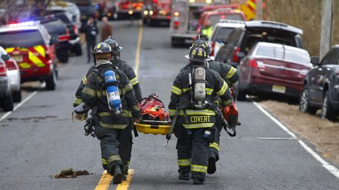 Firefighters carry a stretcher to the scene of a fatal fire on November 20, 2018, in Colts Neck, New Jersey.