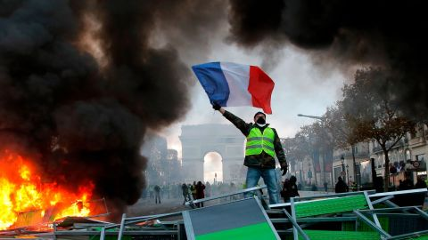 A demonstrator waves the French flag onto a burning barricade on the Champs-Elysees avenue with the Arc de Triomphe in background, during a demonstration against the rising of the fuel taxes, Saturday, Nov. 24, 2018 in Paris. French police fired tear gas and water cannons to disperse demonstrators in Paris Saturday, as thousands gathered in the capital and staged road blockades across the nation to vent anger against rising fuel taxes and Emmanuel Macron's presidency.(AP Photo/Michel Euler)