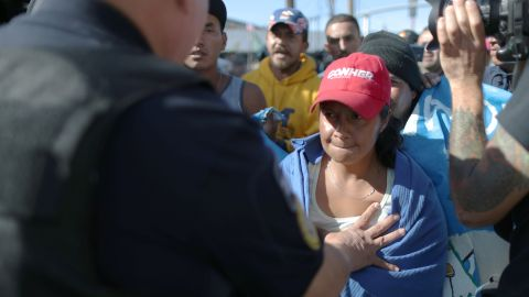 A migrant is pushed back as she attempts to break through a line of Mexican police to reach the border wall.