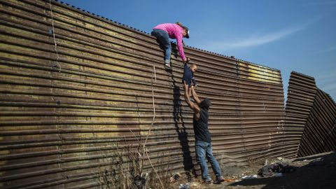 A group of migrants climbs the border fence between Mexico and the United States.
