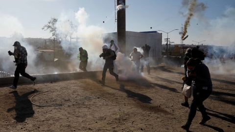 Migrants and journalists run away from tear gas.