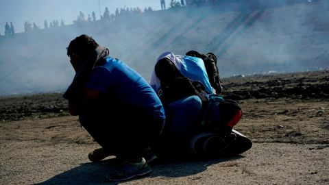 Three Honduran migrants huddle in the riverbank amid tear gas fired by U.S. agents on the Mexico-U.S. border after they and a group of migrants got past Mexican police at the Chaparral border crossing in Tijuana, Mexico, Sunday, Nov. 25, 2018. The mayor of Tijuana has declared a humanitarian crisis in his border city and says that he has asked the United Nations for aid to deal with the approximately 5,000 Central American migrants who have arrived in the city. (AP Photo/Ramon Espinosa)
