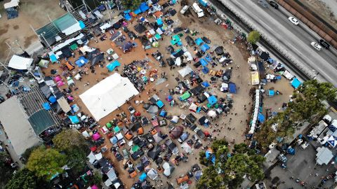 An aerial view of the temporary shelter set up for migrants in Tijuana, with a section of the U.S.-Mexico border barrier visible.