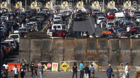 TIJUANA, MEXICO - NOVEMBER 25:  People attempting to cross in the U.S. look on as the San Ysidro port of entry stands closed at the U.S.-Mexico border on November 25, 2018 in Tijuana, Mexico. Migrants circumvented a police blockade as they attempted to approach the El Chaparral port of entry and U.S. Customs and Border Protection temporarily closed the two ports of entry on the border with Tijuana in response. Around 6,000 migrants from Central America have arrived in the city with the mayor of Tijuana declaring the situation a 'humanitarian crisis'.  (Photo by Mario Tama/Getty Images)