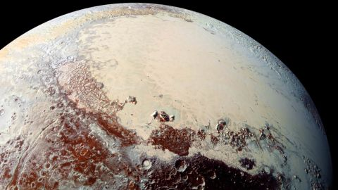 """This high-resolution image captured by NASA's New Horizons spacecraft shows Pluto's surface has a remarkable range of subtle colors, enhanced in this view to a rainbow of pale blues, yellows, oranges, and deep reds. The bright expanse is the western lobe of the """"heart,"""" informally known as Tombaugh Regio. The lobe, informally called Sputnik Planum, has been found to be rich in nitrogen, carbon monoxide, and methane ices."""