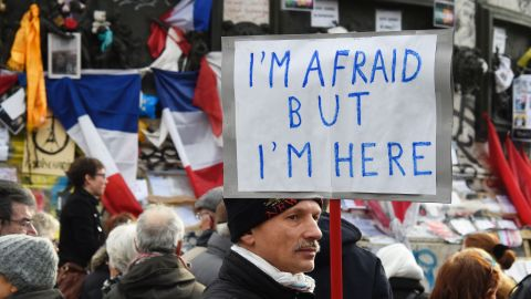 """A man holding a placard reading """"I am afraid but I am here"""" during a gathering on Place de la Republique (Republic square) on January 10, 2016 in Paris, as the city marks a year since 1.6 million people thronged the French capital in a show of unity after attacks on the Charlie Hebdo newspaper and a Jewish supermarket. Just as it was last year, the vast Place de la Republique is the focus of gatherings as people reiterate their support for freedom of expression and remember the other victims of what would become a year of jihadist outrages in France, culminating in the November 13 coordinated shootings and suicide bombings that killed 130 people and were claimed by the Islamic State (IS) group. DOMINIQUE FAGET/AFP/Getty Images"""