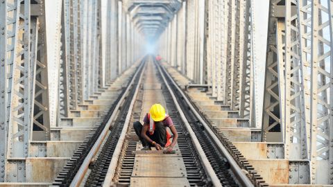 An Indian worker on a railway bridge over the Ganges River in Allahabad on November 30, 2018.