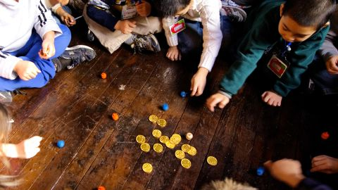NEW YORK - DECEMBER 4:  PS 1 second grade students play with dreidels and chocolate gold coins after lighting the menorah December 4, 2007 at the Eldridge St. Synagogue in New York City. The class was there to learn about Hannukah and also about the newly restored synagogue which originally opened its doors in 1887.  (Photo by Stephen Chernin/Getty Images)