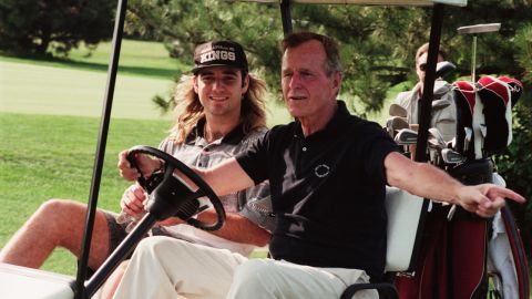 Bush plays golf with tennis player Andre Agassi in 1991.
