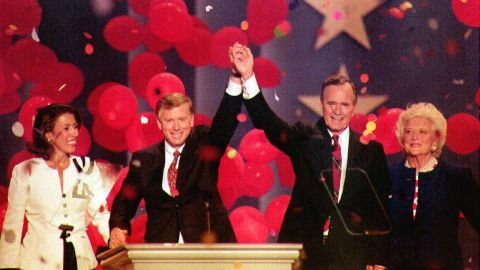 Bush and Vice President Dan Quayle join hands at the 1992 Republican National Convention in Houston. They are joined by their wives, Marilyn Quayle and Barbara Bush.