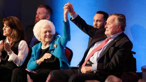 Bush holds up his wife's hand at a Republican presidential debate in 2016. One of their sons, former Florida Gov. Jeb Bush, was among the candidates in the debate.