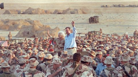 Bush and the first lady wave goodbye to US Marines and British troops after a Thanksgiving Day visit to Saudi Arabia in 1990.