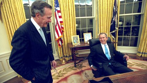 With his father by his side, President George W. Bush sits at his desk in the Oval Office for the first time on Inauguration Day, January 20, 2001.