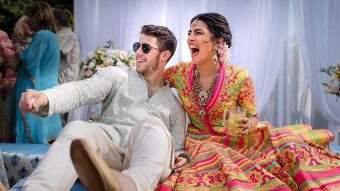 In this Friday, Nov. 30, 2018 handout photo released by Raindrop Media, Bollywood actress Priyanka Chopra and Nick Jonas celebrate during their mehendi ceremony, a day before their wedding, at Umaid Bhawan in Jodhpur, India. (Raindrop Media via AP)