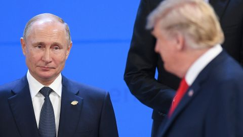 5716955 30.11.2018 Russian President Vladimir Putin, left, looks at U.S. President Donald Trump before posing for a family photo before the G20 summit in Buenos Aires, Argentina, November 30, 2018. Vladimir Astapkovich / Sputnik  via AP