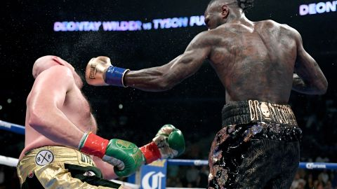 Deontay Wilder knocks Tyson Fury down during the 12th round to earn the draw and retain his belt.