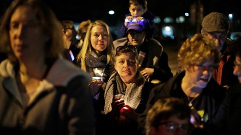 People watch as a menorah is lighted outside the Tree of Life Synagogue on the first night of Hanukkah, Sunday, Dec. 2, 2018 in the Squirrel Hill neighborhood of Pittsburgh. A gunman shot and killed 11 people while they worshipped Saturday, Oct. 27, 2018 at the temple. (AP Photo/Gene J. Puskar)