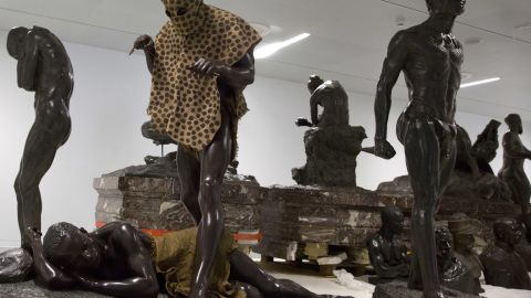A sculpture called the 'Leopard Man', second left, is stored with others in a cavernous room at the Africa Museum in Tervuren, Belgium, Friday, Aug. 3, 2018. The museum is reopening on Saturday Dec. 8, 2018, after more than 10 years spent revamping the building and overhauling its dated, one-sided approach to history. (AP Photo/Virginia Mayo)