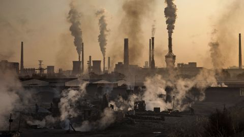 """INNER MONGOLIA, CHINA - NOVEMBER 04: Smoke billows from a large steel plant as a Chinese labourer works at an unauthorized steel factory, foreground, on November 4, 2016 in Inner Mongolia, China. To meet China's targets to slash emissions of carbon dioxide, authorities are pushing to shut down privately owned steel, coal, and other high-polluting factories scattered across rural areas. In many cases, factory owners say they pay informal 'fines' to local inspectors and then re-open. The enforcement comes as the future of U.S. support for the 2015 Paris Agreement is in question, leaving China poised as an unlikely leader in the international effort against climate change. U.S. president-elect Donald Trump has sent mixed signals about whether he will withdraw the U.S. from commitments to curb greenhouse gases that, according to scientists, are causing the earth's temperature to rise. Trump once declared that the concept of global warming was """"created"""" by China in order to hurt U.S. manufacturing. ChinaÍs leadership has stated that any change in U.S. climate policy will not affect its commitment to implement the climate action plan. While the world's biggest polluter, China is also a global leader in establishing renewable energy sources such as wind and solar power. (Photo by Kevin Frayer/Getty Images)"""