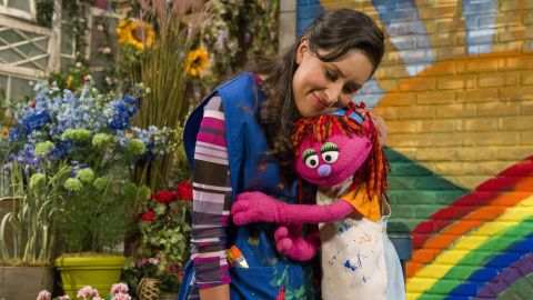 Lily hugs her friend Sofia after painting a rainbow. Lily is a resilient 7-year-old Muppet whose family is staying with friends on Sesame Street after losing their home.