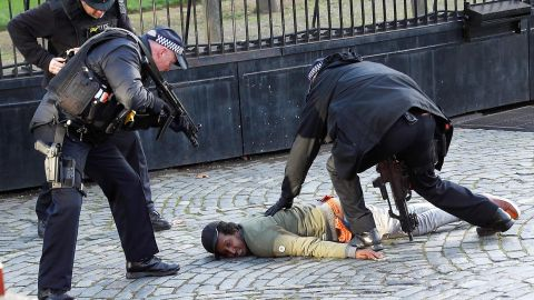 Armed police restrain a man inside the grounds of the Houses of Parliament on Tuesday.