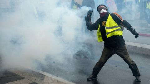 """A protester throws a part of a tear gas canister during a protest of """"yellow vests"""" (gilets jaunes) against rising costs of living they blame on high taxes in Nantes, eastern France on December 8, 2018. - French """"yellow vest"""" demonstrators clashed with riot police in Paris on December 8, 2018 in the latest round of protests against President Emmanuel Macron, but the city appeared to be escaping the large-scale destruction of a week earlier due to heavy security. (Photo by Sebastien SALOM-GOMIS / AFP)        (Photo credit should read SEBASTIEN SALOM-GOMIS/AFP/Getty Images)"""