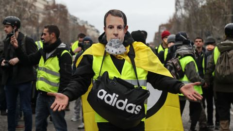 """A protestor wearing a """"yellow vest"""" (gilet jaune) and with a French President Emmanuel Macron mask poses on the Champs Elysees avenue in Paris on December 8, 2018 during protest against rising costs of living they blame on high taxes. - Paris was on high alert on December 8 with major security measures in place ahead of fresh """"yellow vest"""" protests which authorities fear could turn violent for a second weekend in a row. (Photo by Zakaria ABDELKAFI / AFP)        (Photo credit should read ZAKARIA ABDELKAFI/AFP/Getty Images)"""