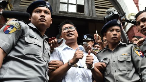 TOPSHOT - Myanmar journalist Wa Lone (C) is escorted by police after being sentenced by a court to jail in Yangon on September 3, 2018. - Two Reuters journalists were jailed on September 3 for seven years for breaching Myanmar's official secrets act during their reporting of the Rohingya crisis, a judge said, a case that has drawn outrage as an attack on media freedom. (Photo by Ye Aung THU / AFP)        (Photo credit should read YE AUNG THU/AFP/Getty Images)