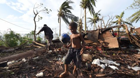 PORT VILA, VANUATU - MARCH 16:  Samuel walk through through the ruins of his family home with his father Phillip, on March 16, 2015 in Port Vila, Vanuatu. Cyclone Pam has hit South Pacific islands on Saturday with hurricane force winds, huge ocean swells and flash flooding and has caused severe damage to housing. Aid agencies say it could be one of the worst disasters ever to hit the region.  (Photo by Dave Hunt-Pool/Getty Images)