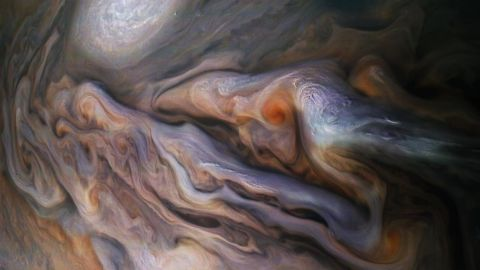 """A multitude of magnificent, swirling clouds in Jupiter's dynamic North North Temperate Belt is captured in this image from NASA's Juno spacecraft. Appearing in the scene are several bright-white """"pop-up"""" clouds as well as an anticyclonic storm, known as a white oval. This color-enhanced image was taken at 1:58 p.m. PDT on Oct. 29, 2018 (4:58 p.m. EDT) as the spacecraft performed its 16th close flyby of Jupiter. At the time, Juno was about 4,400 miles (7,000 kilometers) from the planet's cloud tops, at a latitude of approximately 40 degrees north."""