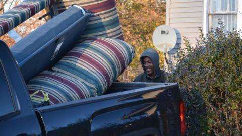 Volunteer Levi Lindsey loads furniture into Guido's pickup truck.