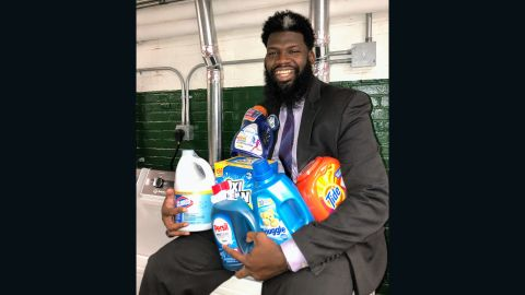 Cook holds an armful of donated laundry products.