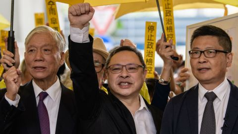 Baptist minister Chu Yiu-ming, 74, law professor Benny Tai, 54, and sociology professor Chan Kin-man, 59, shout slogans with supporters before entering the West Kowloon Magistrates Court in Hong Kong on November 19, 2018.