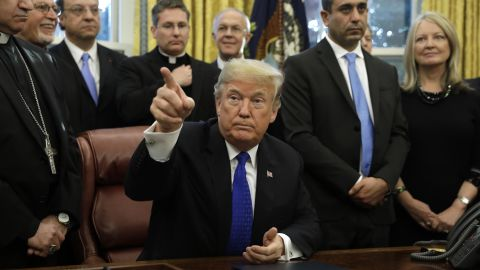 U.S. President Donald Trump takes a question from a member of the media after signing bill H.R. 390, the Iraq and Syria Genocide Relief and Accountability Act of 2018, in the Oval Office of the White House in Washington, D.C., U.S., on Tuesday, Dec. 11, 2018. Trumpstaged a confrontation Tuesday with the two top congressional Democrats before television cameras in the Oval Office as the dispute over funding for his border wall turned publicly acrimonious. Photographer: Yuri Gripas/Bloomberg via Getty Images