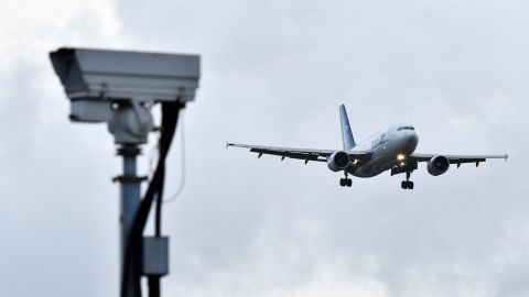 """An Air Transat aircraft is pictured beyond a CCTV camera as it prepares to land at London Gatwick Airport, south of London, on December 21, 2018, as flights resumed following the closing of the airfield due to a drones flying. - British police were Friday considering shooting down the drone that has grounded flights and caused chaos at London's Gatwick Airport, with passengers set to face a third day of disruption. Police said it was a """"tactical option"""" after more than 50 sightings of the device near the airfield since Wednesday night when the runway was first closed. (Photo by Ben STANSALL / AFP)        (Photo credit should read BEN STANSALL/AFP/Getty Images)"""