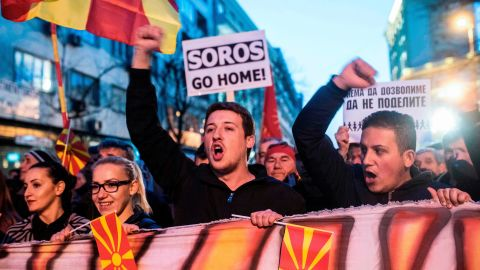 """People wave flags and chant slogans while a man carries a protest sign reading """"SOROS Go Home"""" during a demonstration against a deal between Social Democrats and the Albanian Democratic Union for Integration, for a law making Albanian the second official language, on March 15, 2017 in Skopje. The Macedonian president, who has accused neighbouring Albania of trying to influence political developments across the border, referred to minority ethnic Albanian parties' decision to back opposition chief Zoran Zaev if he accepted their controversial demand to make Albanian an official language across Macedonia.  / AFP PHOTO / Robert ATANASOVSKI        (Photo credit should read ROBERT ATANASOVSKI/AFP/Getty Images)"""
