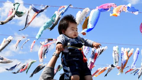 A father holds up his baby under carp streamers fluttering in a riverside park in Sagamihara, suburban Tokyo, on April 29, 2016, ahead of May 5 Children's Day in Japan.