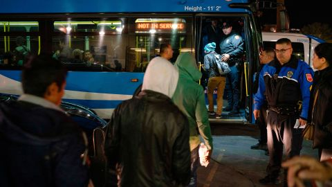 Migrants board buses Sunday night in El Paso after ICE officials dropped them off earlier.