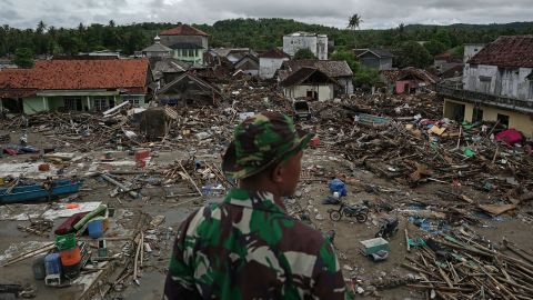 An Indonesian soldier looks at damaged houses and debris after a tsunami in Sumur, Pandeglang, Banten province, Indonesia, on Tuesday, Dec. 25, 2018. The death toll from a tsunami along Indonesias Sunda Strait exceeded 400 as rescuers scour through the wreckage of hundreds of hotels and houses flattened by the deadly wave. Photographer: Dimas Ardian/Bloomberg via Getty Images