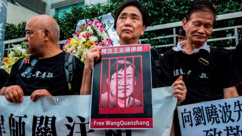 Hong Kong former lawmaker Emily Lau (C) holds a sign of detained Chinese human rights lawyer Wang Quanzhang at a rally outside the Chinese Liaison Office in Hong Kong on April 5, 2018, to commemorate human rights activists and call for the release of political prisoners. / AFP PHOTO / ISAAC LAWRENCE        (Photo credit should read ISAAC LAWRENCE/AFP/Getty Images)