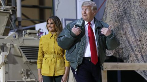 The Trumps walk onstage to speak at a hangar rally during their surprise visit.