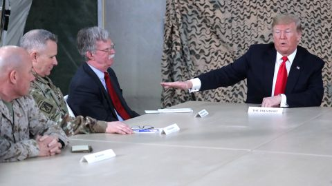President Trump, flanked by National Security Adviser John Bolton, near left, meets with military leaders during his unannounced visit.
