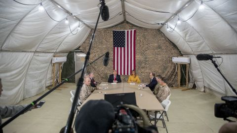 President Trump, accompanied by National Security Adviser John Bolton, third from left, first lady Melania Trump, fourth from right, US Ambassador to Iraq Doug Silliman, third from right, and senior military leadership, speaks to members of the media during his surprise visit to Iraq.
