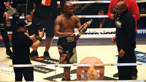 Floyd Mayweather holds the trophy aloft after beating his youthful opponent Tenshin Nasukawa at the Saitama Super Arena in Japan.